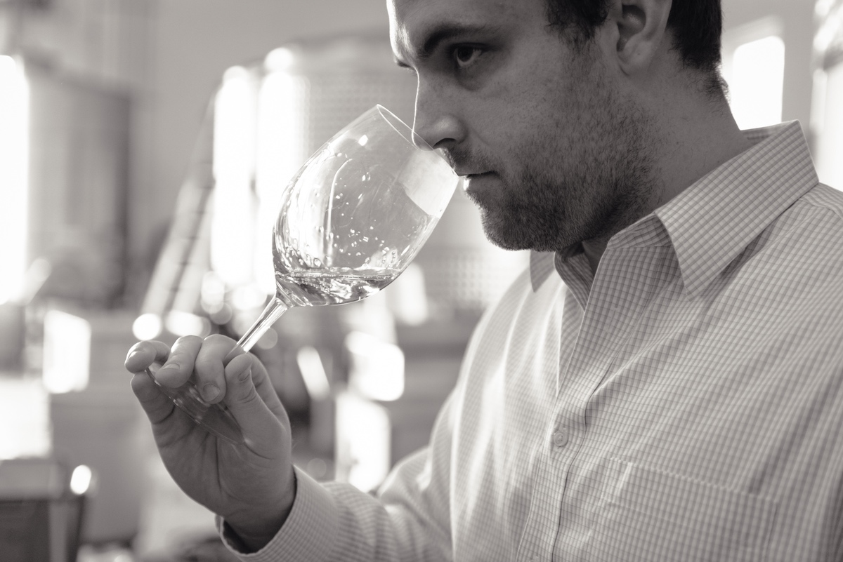 Cameron Metzker smelling the aromatics from a glass of the Metzker Family's Ritchie Vineyard Chardonnay.