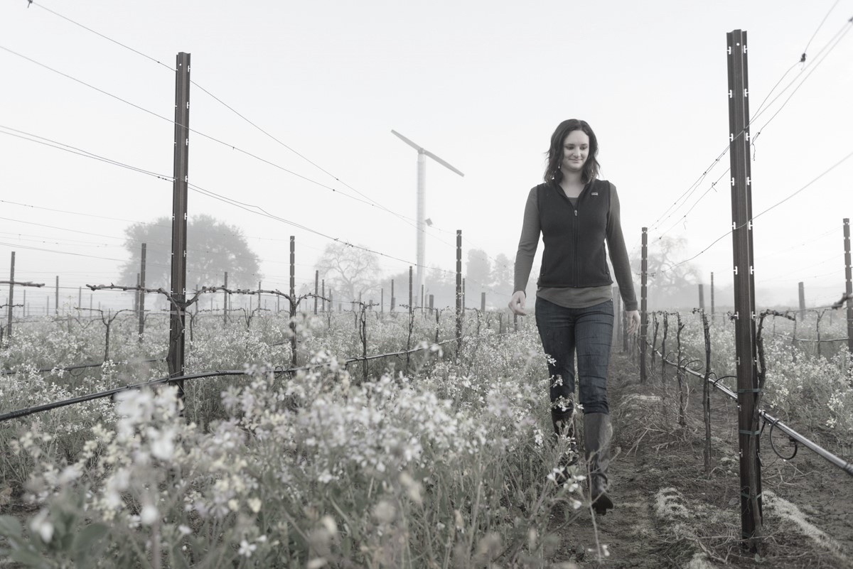 Melissa Castro walking through the Cabernet Sauvignon vines of the Spring Mountain District Vineyard on an overcast day during the winter.